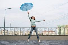 Flickan flyger med ett paraply Fotografering för Bildbyråer
