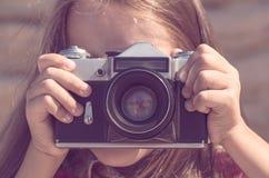 Flickan fotograferar en gammal sovjetisk kamera i brun tonting royaltyfria bilder