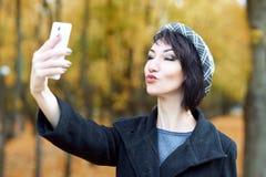 Flickan fotograferar sig på telefonen, och kyssar i höststad parkerar, gulingsidor och träd, nedgångsäsong Arkivbild