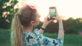 Flickan fotograferar solnedgången på telefonen tillbaka beskådar långsam-mo stock video