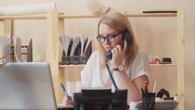 Flickan från servicemitten väljer upp telefonen, svar och sätter den ner, är hennes medarbetare och ger därefter hennes fem lager videofilmer