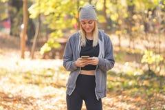 Flickan från telefonen i skogen läser ett meddelande royaltyfria bilder