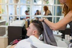 Flickan frisören tvättar hennes hår, når han har klippt den unga stiliga grabben i skönhetsalongen Royaltyfria Foton