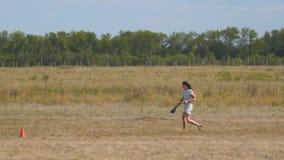 Flickan går över ett fält med torrt gräs stock video