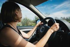 Flickan går bak hjulet av en bil Royaltyfri Bild