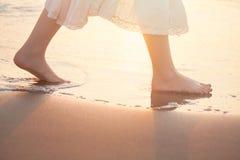 Flickan går barfota på stranden i vatten royaltyfri fotografi