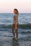 Flickan går in i havet Arkivbild