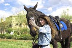 Flickan går i natur och poserar nära en häst royaltyfria foton