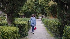Flickan går i parken längs de skräddarsydda gröna buskarna och för henne över bladen. arkivfilmer