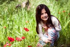 Flickan går i skogen var vallmo blommar Royaltyfri Foto