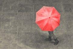Flickan går med paraplyet i regn på konstnärlig omvandling för trottoar Arkivfoto