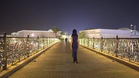 Flickan går in mot en man på ett datum Den eleganta kvinnan i aftonkappa går för att möta en pojkvän på den tomma staden för natt arkivfilmer