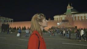 Flickan går och beundrar den röda fyrkanten för natten och Kreml i Moskva stock video