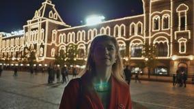 Flickan går och beundrar den röda fyrkanten för natten och Kreml i Moskva arkivfilmer