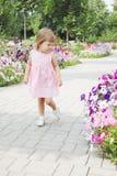 Flickan går på en blommagränd Arkivbild