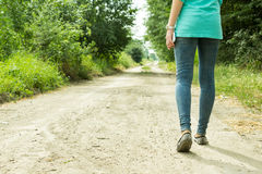 Flickan går på en grusväg med en telefon Royaltyfri Foto