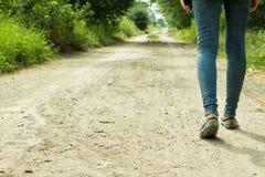 Flickan går på en grusväg till och med träden Royaltyfri Foto