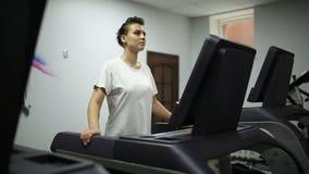 Flickan går på en trampkvarn i idrottshallen lager videofilmer