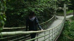 Flickan går på en upphängningbro i en tät skog arkivfilmer