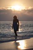Flickan går på stranden under soluppgången Royaltyfria Bilder