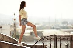 Flickan g?r p? taket Stad p? bakgrund fotografering för bildbyråer