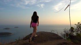 Flickan går playfully till observationsdäcket Hår som fladdrar i vinden, bärande exponeringsglas lager videofilmer