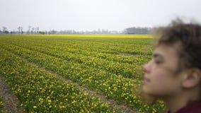 Flickan går till och med ett fält av blommor arkivfilmer