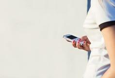 Flickan går till och med staden och den gnric telefonen i händer Arkivfoto