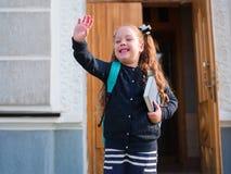Flickan går till skolan med en portfölj och en bok arkivfoton