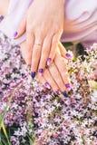 Flickan gömma i handflatan i delikat färg med en bukett av blommor royaltyfri bild