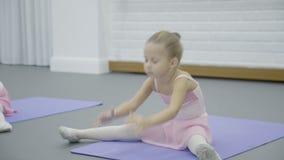 Flickan gör den kluvna kroppen för halvan böjde under balettgruppen i härlig studio lager videofilmer