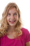 Flickan gör den roliga framsidan i closeup över vit bakgrund Royaltyfria Bilder