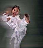 Flickan gör den Taekwondo sparken Arkivbild