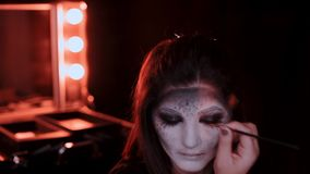Flickan gör ett smink i stilen av en häxaallhelgonaafton arkivfilmer