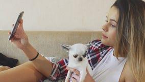 Flickan gör fotoet med hunden royaltyfria bilder