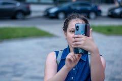 Flickan gör fotoet på smartphonen flicka f?r modernt liv med smartphonen fotografering för bildbyråer