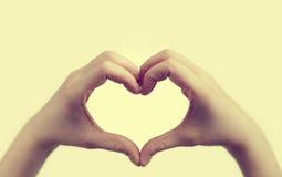 Flickan gör hjärta att forma med händer Arkivbild