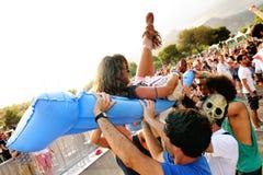 Flickan gör kroppen som surfar över en uppblåsbar madrass på Los Tiki Phantoms för att sätta band show på FIB Fotografering för Bildbyråer