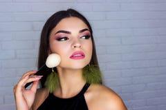 Flickan gör makeupframsidaborsten för makeup arkivfoto
