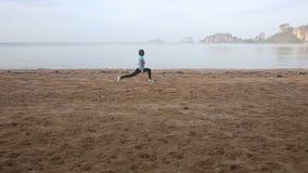 flickan gör morgonövningar på stranden på gryning mot klippor lager videofilmer