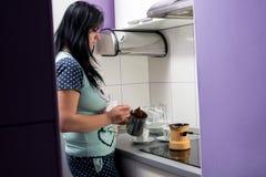 Flickan gör morgonkaffe Fotografering för Bildbyråer