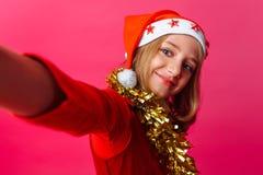 Flickan gör på en selfie i hatten av Santa Claus och glitter royaltyfri foto