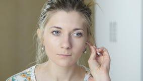 Flickan gör ren öronen med en pinne stock video