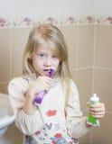Flickan gör ren hennes tänder och rymmer en tandkräm i henne händer Arkivbilder
