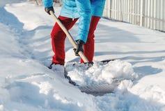 Flickan gör ren snöskyffeln på platsen nära hans hus solljus royaltyfri fotografi