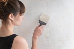 Flickan gör reparationen av lägenheten royaltyfri bild