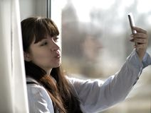 Flickan gör selfie, medan sitta vid fönstret arkivfoto