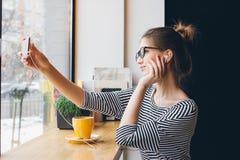 Flickan gör selfie på smartphonen i coffee shop Arkivbilder