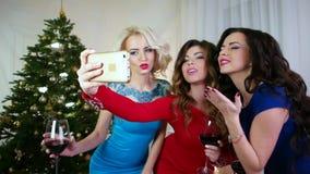 Flickan gör selfiefotoet, nyårsaftonen, en härlig ung kvinna som firar jul på ett parti, mobiltelefon i handflicka lager videofilmer