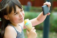 Flickan gör självporträttet på smartphonen Arkivfoton